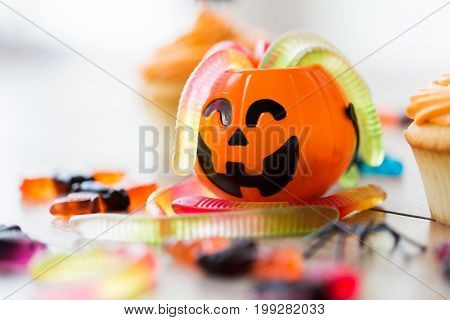 halloween, junk food and confectionery concept concept - multicolored gummy worms and candies with jack-o-lantern decoration on table
