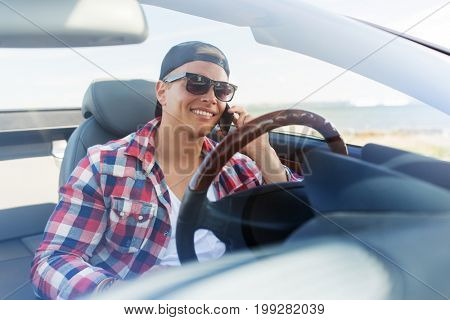 summer holidays, travel, road trip and people concept - happy young man calling on smartphone in convertible car