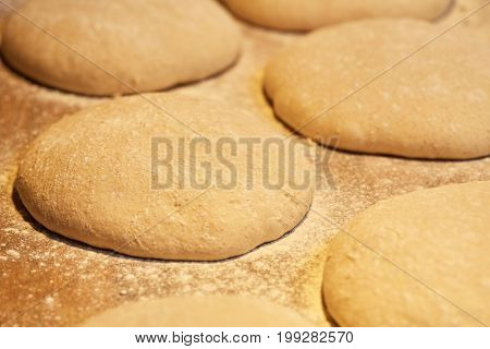 food, cooking and baking concept - close up of yeast bread dough rising at bakery