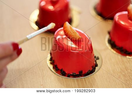 cooking, baking and food concept - chef with brush decorating strawberry mirror glaze cakes with edible gold at confectionery