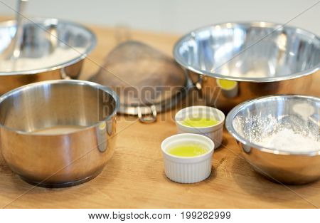 cooking food and baking concept - bowls with flour and egg whites at bakery kitchen