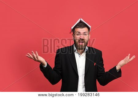 Man In Classic Outfit With Beard Holds Book On Head