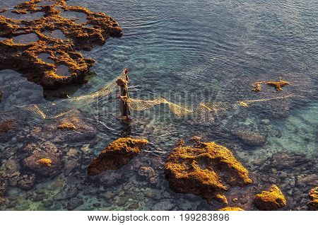 Fisherman with the nat catching fish in the ocean Indonesia
