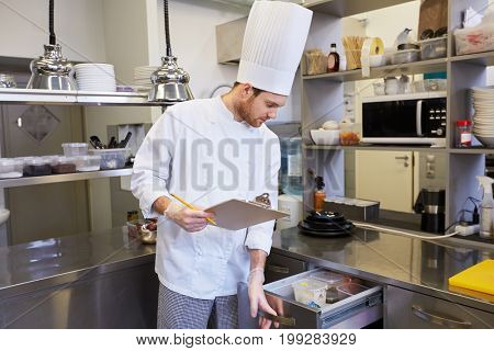 cooking, profession and people concept - male chef cook with clipboard doing inventory and looking to fridge at restaurant kitchen