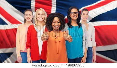 diversity, ethnicity and people concept - international group of happy smiling different women showing thumbs up over english flag background