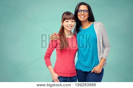 school, education and people concept - two happy smiling international women students over green chalk board background