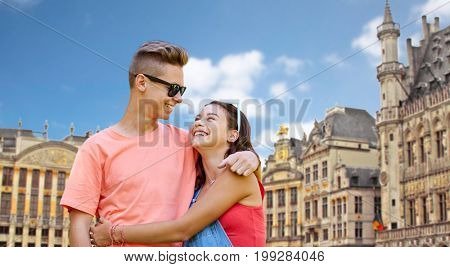 travel, tourism and people concept - happy smiling teenage couple hugging and looking at each other over grand place in brussels city background