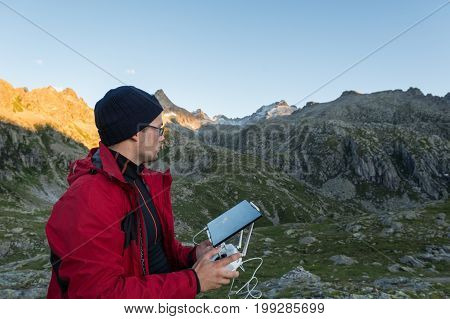 Man flying a drone. Making aerial footage in mountains.
