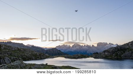 Drone flying above mountain lake. Laghi di Cornisello, Brenta group in Italy.