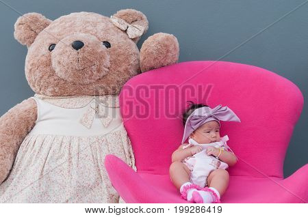 A shot of a cute baby girl with purple headband and big teddy bear while sleeping and playing on the pink chair /  Focus at infant girl with teddy bear on gray background