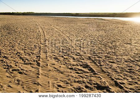 Car track on the sand in the desert .