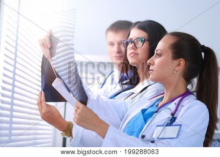Young group of doctors looking at x-ray .
