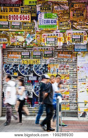 HONG KONG - JULY 10 2017: Posters flyers and advertisements fill every inch of a wall in the busy downtown district of Mong Kok as pedestrians hurried by.