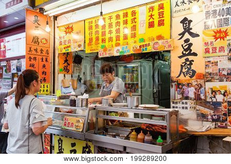HONG KONG - JULY 10 2017: A street vendor selling stinky tofu sausages fishball cutterfish and beef intestines in Mong Kok. Eating street food is part of the Hong Kong culture.