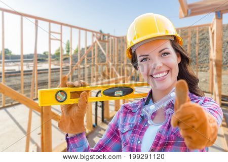 Female Construction Worker with Thumbs Up Holding Level Wearing Gloves, Hard Hat and Protective Goggles at Construction Site.