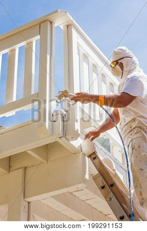 Professional House Painter Wearing Facial Protection Spray Painting Deck of A Home.