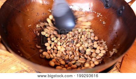 Coffee beans are roasting in pan. Traditional techniques.