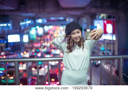 Happy asian woman taking selfie joyful and happy smiling at night