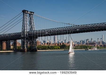 Sailboat passes under the Williamsburg bridge that connects Manhattan with Brooklyn