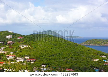 Landscape of St Thomas Island with houses mountains and distant islands on the horizon US VI. Tropical island in early morning.