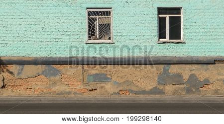 Fragment of a very old building, old architecture, two windows, old building, foundation