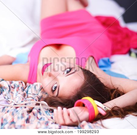 Happy woman lying bed surrounded by her clothes .