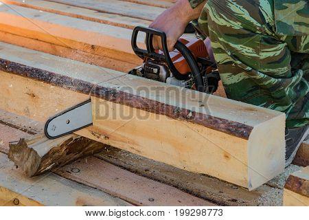 Man, builder, carpenter saws petrol chainsaw new hardwood timber, a building material, timber
