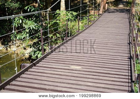 wood sling bridge in forest at Kanchanaburi Thailand