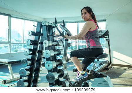 Young asian woman doing sport in the gym for fitness