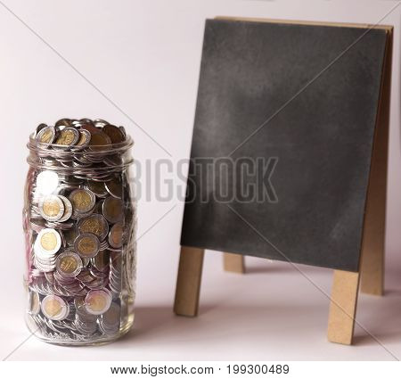 glass jar with full of mexican pesos coins and blackboard