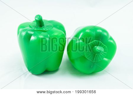 Plastic fake toy greeen Bell pepper isolated on white background