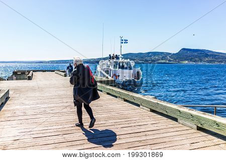 Perce Canada - June 6 2017: Bonaventure Island Park entrance in Gaspe Peninsula Quebec Gaspesie region with woman walking to boat ferry on dock pier