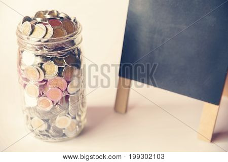 glass jar with full of mexican pesos coins and black board with vintage color tone process