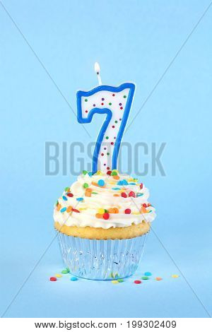 Iced birthday cupcake with with lit number 7 candle and sprinkles