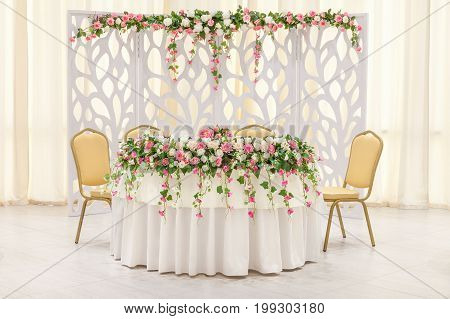 The main table of the newlyweds decorated with a floral composition and an arch in pastel colors.