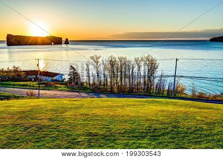 Famous Rocher Perce rock in Gaspe Peninsula Quebec Canada Gaspesie region with cityscape at sunrise and sun
