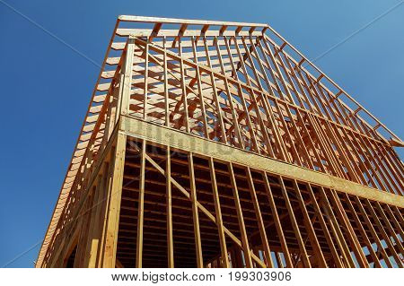 A Single Family Home Under Construction. The House Has Been Framed And Covered In Plywood.