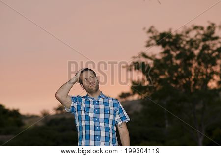 Man with one hand on his head thinking about what tomorrow brings at dusk.