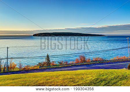 Bonaventure Island during sunrise in Gaspe Peninsula Quebec Canada Gaspesie region with blue water and illuminated grass