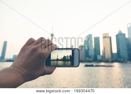 using smart phone to record beautiful scenery of the bund in the morning,shanghai,china.
