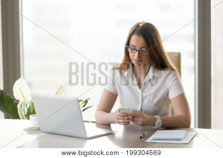 Attractive businesswoman holding smartphone, texting message while sitting at workplace, using apps, banking application, person dialing number, adding reminder, important note on phone, mobile office