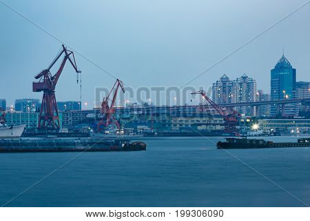 Ships on Huangpu River and cranes at the harbour,shanghai,china.