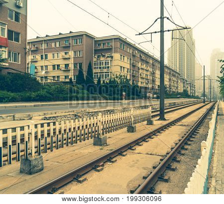 empty railway tracks by residential district,vintage toned,tianjin,china.