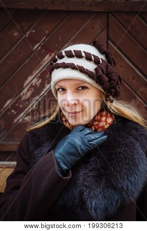 Young woman winter portrait with hat, brown coat and black leather gloves, outdoor.