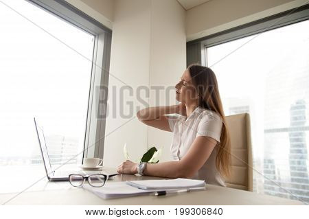 Tired businesswoman feeling discomfort at workplace, massaging tense muscles, suffering from chronic neck pain after long work on laptop computer, sedentary job, incorrect posture, office syndrome