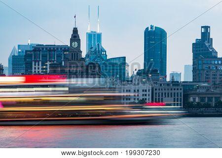 the bund skyline with blurred cruise boat on huangpu river,shanghai,china.