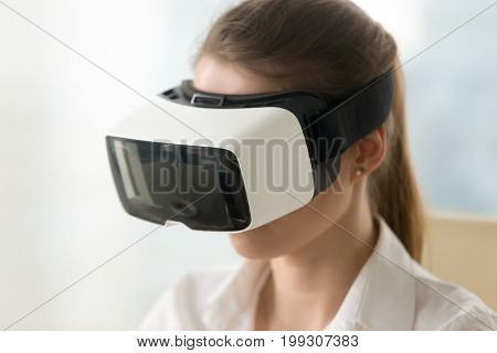 Young woman wearing vr glasses, first experience of using innovative headset for gaming and business, virtual office, modern educational technology, augmented world immersion, portrait head shot