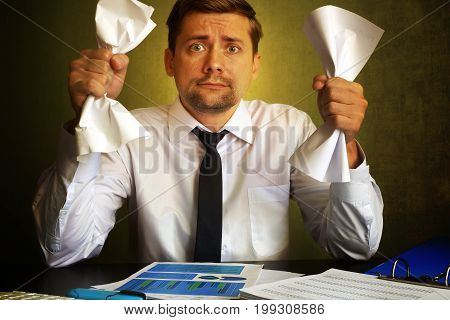 Nervous businessman observing bills. Problems in a business.