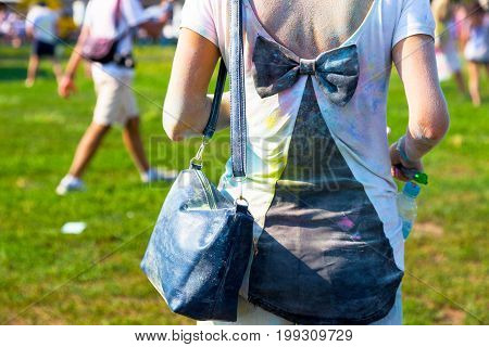 Girl In T-shirt With Bowknot On The Back. Back And T-shirt Sprinkled With Colored Paints Powders Dur