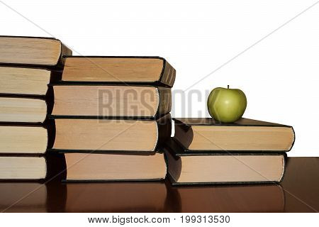 Books and an apple on a brown wooden table